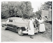 view Outdoor Photo of Two Women with a Man and Child on the Hood of a Car digital asset number 1
