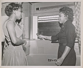 view Photograph of a young woman demonstrating use of voting machine digital asset number 1