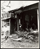 view Photograph of a girl walking in front of a looted store after the Newark Riots digital asset number 1