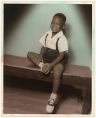 view A hand-tinted photograph of a smiling boy in suspenders and saddle shoes digital asset number 1
