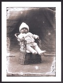 view Print of a baby sitting in a wicker chair digital asset number 1