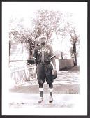view Print of a man in a baseball uniform standing on the sidewalk digital asset number 1