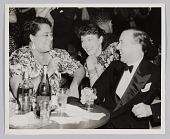 view Photograph of a man and two women seated at a table digital asset number 1