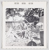 view Photographic print of Cliff Jackson sitting next to a pile of scrap wood digital asset number 1