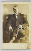 view Photographic postcard of a seated man holding a bowler hat digital asset number 1