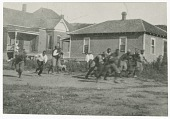 view Photograph of men running with a football in front of two houses digital asset number 1