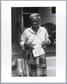 view Photograph of Mary Reid holding flyer featuring swastikas and hate language digital asset number 1
