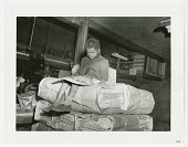 view Photograph of girl reading on a pallet of newspapers at the Pittsburgh Courier digital asset number 1