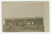 view Postcard of men, women, and children outside of a dwelling digital asset number 1
