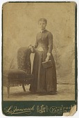 view Photograph of a woman standing next to a chair and holding a book digital asset number 1