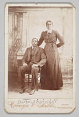 view Photograph of a man sitting down with a woman standing next to him digital asset number 1
