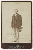 view Photograph of young man holding a hat and gloves digital asset number 1