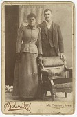 view Photograph of a couple standing behind a chair digital asset number 1