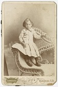 view Photograph of a toddler standing on a wicker chair digital asset number 1