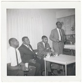 view Photographic print of four men sitting around a table digital asset number 1