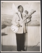 view Gelatin silver print of Monk Montgomery singing and playing the guitar digital asset number 1