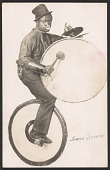 view Postcard of a performer playing a drum while on a unicycle digital asset number 1