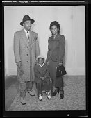 view Studio Portrait of a Mother and Father Standing, Child is Sitting on a Chair digital asset number 1