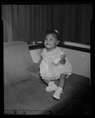 view Studio Portrait of a Toddler Girl Sitting on a Sofa Holding a Bottle digital asset number 1