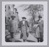 view Photo of a woman in fur standing between two men on the sidewalk digital asset number 1