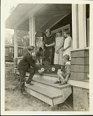 view [Young man demonstrating a radio to a woman, two girls and a boy on the front porch of a house, black-and-white photoprint.] digital asset: [Young man demonstrating a radio to a woman, two girls and a boy on the front porch of a house, black-and-white photoprint.]