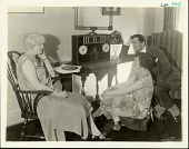 view [Two women and a man seated around a tabletop radio, black-and-white photoprint.] digital asset: [Two women and a man seated around a tabletop radio, black-and-white photoprint.]