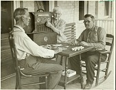 view [Two men playing dominoes and woman adjusting a radio dial on a porch, black-and-white photoprint.] digital asset: [Two men playing dominoes and woman adjusting a radio dial on a porch, black-and-white photoprint.]
