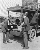 view [Man showing a radio to another man from the back of a truck, black-and-white photoprint.] digital asset: [Man showing a radio to another man from the back of a truck, black-and-white photoprint.]