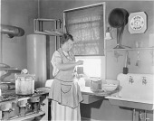view [Woman in kitchen; canning and listening to the radio, black-and-white photoprint.] digital asset: [Woman in kitchen; canning and listening to the radio, black-and-white photoprint.]