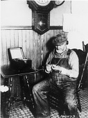 view [Man looking at pocket watch and listening to radio with headphones, black-and-white photoprint.] digital asset: [Man looking at pocket watch and listening to radio with headphones, black-and-white photoprint.]