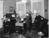 view [Three women, two men and a boy in room with piano listening to the radio, black-and-white photoprint.] digital asset: [Three women, two men and a boy in room with piano listening to the radio, black-and-white photoprint.]