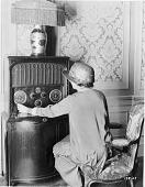 view [Woman adjusting radio dial, black-and-white photoprint.] digital asset: [Woman adjusting radio dial, black-and-white photoprint.]
