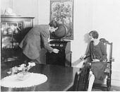 view [Man adjusting radio dial while woman watches, black-and-white photoprint.] digital asset: [Man adjusting radio dial while woman watches, black-and-white photoprint.]