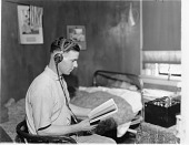 view [Man wearing headphones to listen to the radio while looking at a book, black-and-white photoprint.] digital asset: [Man wearing headphones to listen to the radio while looking at a book, black-and-white photoprint.]