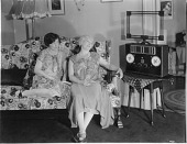 view [Two women listening to the radio, black-and-white photoprint.] digital asset: [Two women listening to the radio, black-and-white photoprint.]