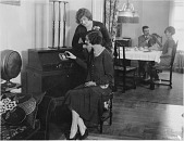view [Two women adjusting a radio dial with a man and woman seated at a table in the background, black-and-white photoprint.] digital asset: [Two women adjusting a radio dial with a man and woman seated at a table in the background, black-and-white photoprint.]