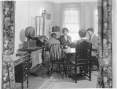 view [Two women and two men playing cards while one man adjusts a radio dial, black-and-white photoprint.] digital asset: [Two women and two men playing cards while one man adjusts a radio dial, black-and-white photoprint.]