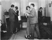 view [Two couples dancing while another woman adjusts a radio, black-and-white photoprint.] digital asset: [Two couples dancing while another woman adjusts a radio, black-and-white photoprint.]