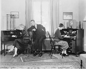 view [A woman adjusting a radio while a man looks on; a second woman writing at a desk, black-and-white photoprint.] digital asset: [A woman adjusting a radio while a man looks on; a second woman writing at a desk, black-and-white photoprint.]