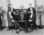 view [Four men in tuxedos standing or sitting around a radio, black-and-white photoprint.] digital asset: [Four men in tuxedos standing or sitting around a radio, black-and-white photoprint.]