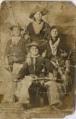 view [Four men wearing cowboy clothing with guns and a lariat: b&w photoprint] digital asset: [Four men wearing cowboy clothing with guns and a lariat: b&w photoprint]