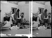 view [Man does laundry while woman, wearing plaid cycling costume, prepares to go out riding on her bicycle. Active no. 70 : stereo photonegative.] digital asset: [Man does laundry while woman, wearing plaid cycling costume, prepares to go out riding on her bicycle. Active no. 70 : stereo photonegative.]