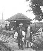 """view [Man holding luggage, with well-dressed woman at railway station with """"Arcola"""" sign. Active no. 9413a : half-stereo photonegative.] digital asset: [Man holding luggage, with well-dressed woman at railway station with """"Arcola"""" sign. Active no. 9413a : half-stereo photonegative.]"""