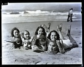 view [Four young women in bathing suits, lying prone on beach, smiling and holding large masks. Non-stereo photonegative.] digital asset: [Four young women in bathing suits, lying prone on beach, smiling and holding large masks. Non-stereo photonegative.]