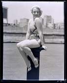 view [Young woman in swimsuit, posed provocatively on a pedestal. Black-and-white photonegative.] digital asset: [Young woman in swimsuit, posed provocatively on a pedestal. Black-and-white photonegative.]