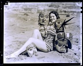 view [Attractive young woman in bathing suit with masks : black-and-whtie photonegative, non-stereo.] digital asset: [Attractive young woman in bathing suit with masks : black-and-whtie photonegative, non-stereo.]