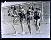 view [Four smiling young women, standing on beach, each holding a mask : black-and-white photonegative, non-stereo.] digital asset: [Four smiling young women, standing on beach, each holding a mask : black-and-white photonegative, non-stereo.]