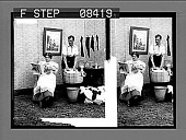 view [Woman seated and reading a magazine, man standing and doing the washing.] Active no. 106 : Photonegative digital asset: [Woman seated and reading a magazine, man standing and doing the washing.] Active no. 106 : Photonegative.
