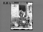 view [African American man playing with mischievous boy in rustic home. Active no. 21953 : half-stereo photonegative.] digital asset: [African American man playing with mischievous boy in rustic home. Active no. 21953 : half-stereo photonegative.]