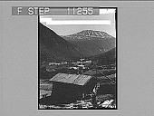 view Snowy rock-ribbed heights of Mt. Gausta (6,180 ft.), towering over quiet homes in the Maan Valley. [Active no. 619 : half-stereo photonegative,] 1905 digital asset number 1